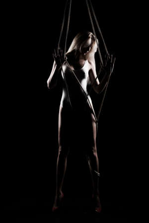 Beautiful slender blonde girl, wearing a white bodisuit and red stilettos, sensually plays and poses with the ropes. Black background. Artistic noir silhouette photo. Copy space. 写真素材