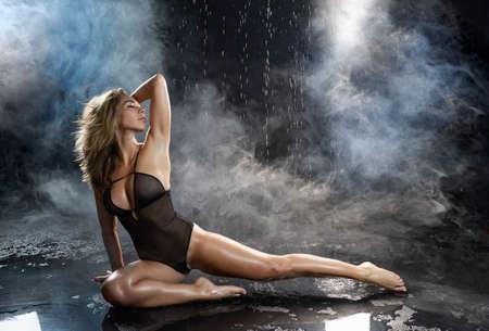 Hermosa chica botín de grandes pechos, vestida con un cuerpo negro translúcido, sentada sensualmente en el piso bajo gotas de agua en humo teatral. Diseño publicitario y comercial. Copie el espacio.