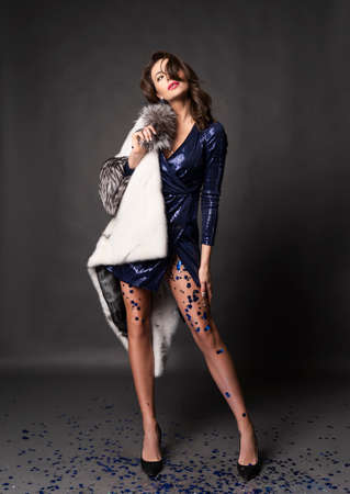Beautiful elegant brunette woman wearing a brilliant blue dress and a fur coat, with her legs covered with glitter stars, is posing on a gray background. Advertising and commercial design. Copy space. Zdjęcie Seryjne