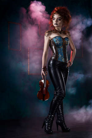 Beautiful redhead cosplayer girl wearing a steampunk corset and leather pants with a big holds violin in her hand in theatrical smoke. Copy space.