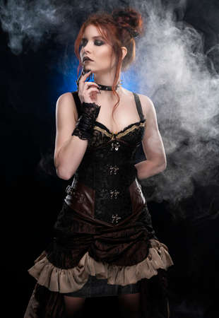 A beautiful redhead cosplayer girl wearing a Victorian-style steampunk costume with a big breast in a deep cleavage standing thoughtfully in a puff of smoke on a black background. Copy space.