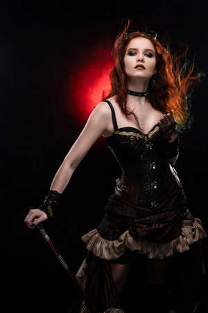 Beautiful redhead cosplayer girl wearing a Victorian-style steampunk costume with a big in a deep neckline and hair blown by the wind rests on a cane. Red and black background. Copy space.