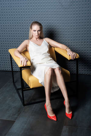 A beautiful blonde girl wearing a light white dress and red stilettos shoes is sitting on a yellow leather chair. Advertising, trendy and commercial design. Copy space. Stockfoto - 119975356