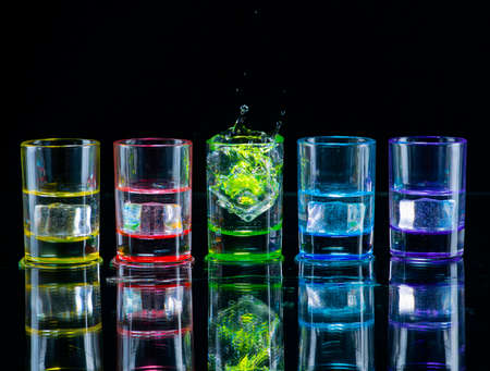 Multicolored glasses filled with alcoholic drinks, with splases of ice cubes falling inside, standing on the mirror surface. Black background. Conceptual, celebrated, commercial design. Closeup.