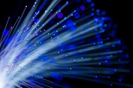 Fotografía conceptual abstracta de hilos de fibra brillando con luz azul. Fondo negro. De cerca.