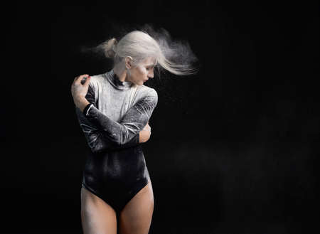 Beautiful slim girl wearing a black gymnastic bodysuit covered with white powder hugs herself and dust flies from her hair on a dark. Artistic conceptual photo. Copy space