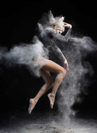 Mooi slank meisje draagt een zwarte gymnastiek bodysuit bedekt met wolken van de vliegende witte poedersprongen die dansen op een donker. Artistieke conceptuele en reclamefoto. Ruimte kopiëren Stockfoto