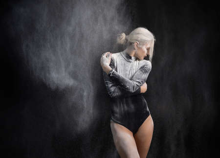Beautiful slim girl wearing a black gymnastic bodysuit covered with clouds of the flying white powder dances on a dark background. Artistic conceptual and advertising photo. Copy space