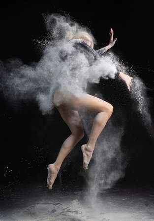 Beautiful slim girl wearing a black gymnastic bodysuit covered with clouds of the flying white powder jumps dancing on a dark. Artistic conceptual and advertising photo. Copy space Фото со стока
