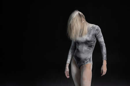Beautiful slim girl wearing a black gymnastic bodysuit covered with white powder talcum dust jumps dances on a dark. Artistic conceptual and advertising photo. Copy space