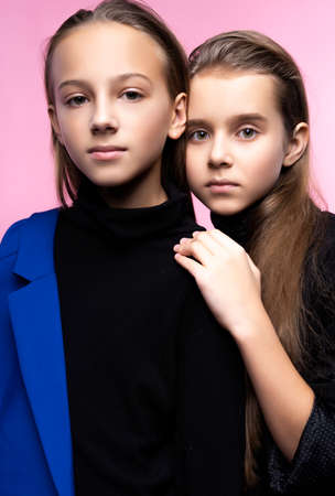 Two cute teenage girlfriends schoolgirls wearing trendy turtleneck sweaters, jeans and blue blazer, hug friendly and posing on pink background. Fashion and advertising design. Copy space. Фото со стока