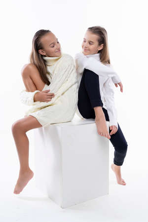 Two cute teenage girlfriends schoolgirls wearing white turtleneck sweaters, smiling sit back to back. Isolated on white. Fashion and advertising design. Copy space.