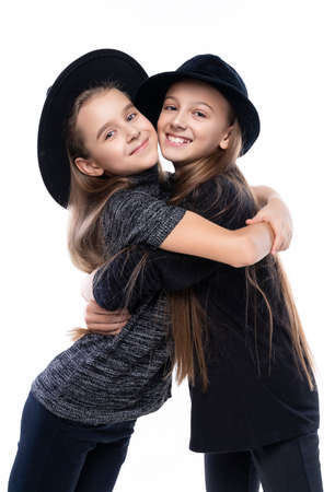 Two cute teenage girlfriends schoolgirls wearing turtleneck sweaters, jeans and hats, smiling hug each other. Isolated on white. Fashion and advertising design. Copy space. Фото со стока