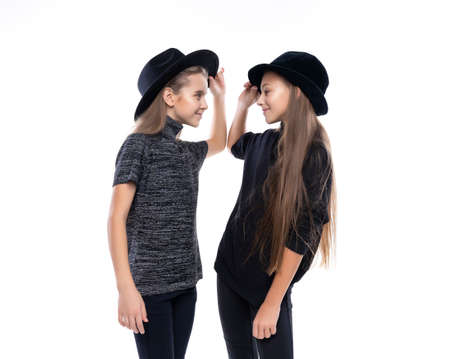 Two cute teenage girlfriends schoolgirls wearing turtleneck sweaters, jeans and hats, smiling dancing and look on each other. Isolated on white. Fashion and advertising design. Copy space. Фото со стока