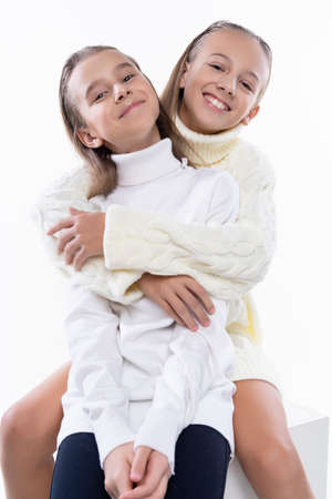 Two cute teenage girlfriends schoolgirls wearing white turtleneck sweaters, smiling sit, hugging each other in a friendly way. Isolated on white. Fashion and advertising design. Copy space.