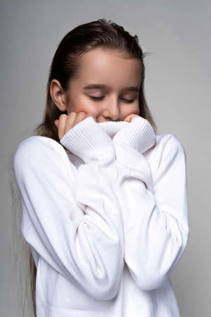 Portrait of a cute smiling teen girl wearing a white turtleneck sweater. Isolated on gray background. Advertising, trendy and commercial design. Copy space. Close-up.