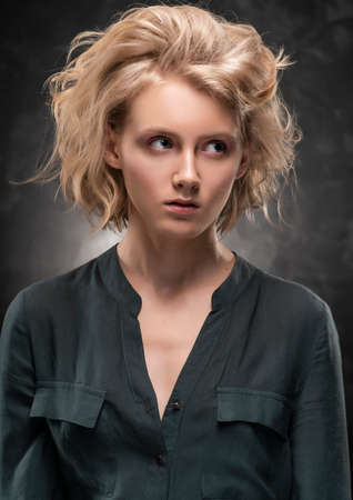 Beautiful young blonde girl with disheveled hairstyle and makeup, wearing a shirt and jeans emotionally posing on gray background. She looks to side and there is madness in her eyes. Copy space