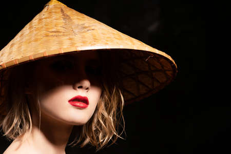 Close-up face of a beautiful young blonde girl with red lips and eyes hidden in the shadow of a cone-shaped Asian cane hat. Clean, healthy skin. Fashionable and advertising design. Copy space.
