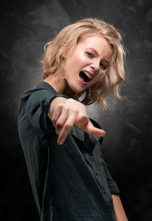 Beautiful young blonde girl with disheveled hair and nude makeup, wearing a shirt and jeans emotionally posing on a gray background. She screams and points a finger. Copy space.