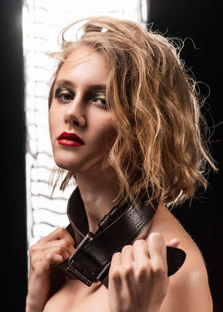 Conceptual portrait of a blonde girl with disheveled wet hair, oily skin, aggressive make-up, and a men's leather belt around her neck against the background of studio light. Copy space. Close-up.