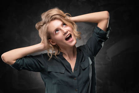 Beautiful young blonde girl with disheveled hairstyle and nude makeup, wearing a shirt and jeans emotionally posing on a gray background. She screams and holds on to her head. Copy space