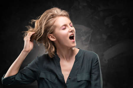 Beautiful young blonde girl with disheveled hairstyle and nude makeup, wearing a shirt and jeans emotionally posing on a gray background. She screams and pulls back her hair. Copy space. Фото со стока