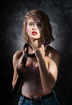 Conceptual photo of a young girl with disheveled wet hair, naked shoulders, aggressive make-up, and a mens leather belt around her neck on a gray background in artistic shadows. Copy space. Фото со стока