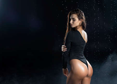 Beautiful leggy and booty athletic fitness girl model, wearing a black body, with wet oily skin, posing under water drops in theatrical smoke on a black background. Copy space. Imagens - 122329294