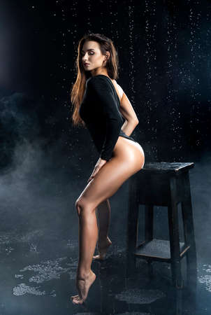 Beautiful leggy and booty athletic fitness girl model, wearing a black body, with wet oily skin, posing on the chair under water drops in theatrical smoke on a black background. Copy space. Фото со стока