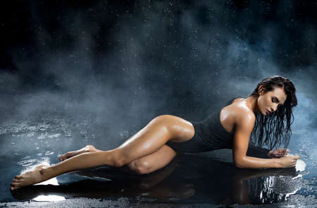 Beautiful leggy and booty athletic fitness girl model, wearing a black body, with wet oily skin, lays on the floor under water drops in theatrical smoke on a black background. Copy space.
