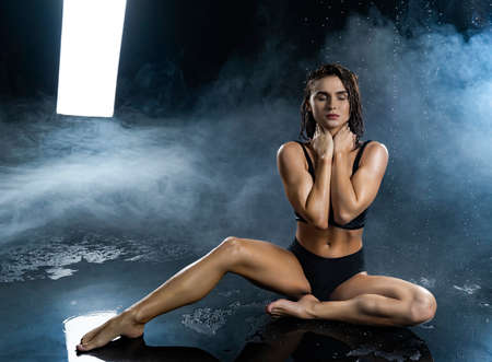 Beautiful leggy and booty athletic fitness girl model, wearing a black sport underwear, with wet oily skin, rests sitting under water drops in theatrical smoke on a black background. Copy space.