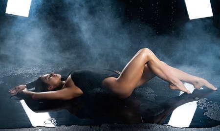 Hermosa modelo de chica fitness atlético de piernas largas y botín, vestida con un cuerpo negro, con la piel grasa húmeda, yace en el suelo bajo gotas de agua en humo teatral sobre un fondo negro. Copie el espacio.
