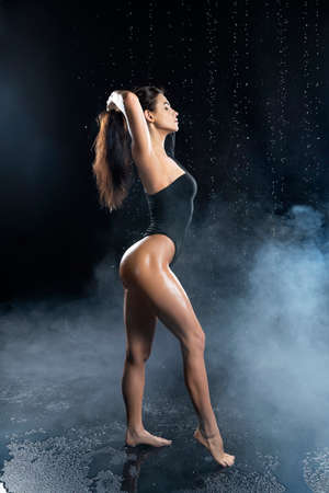 Beautiful leggy and booty athletic fitness girl model, wearing a black body, with wet oily skin, posing under water drops in theatrical smoke on a black background. Copy space.