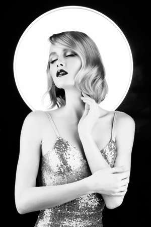 Cute face blond girl with red lips and vintage style hairstyle, wearing a golden sparkling dress with a halo behind her head touches her face and close her eyes. Black and white. Copy space. Фото со стока