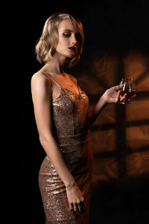 Cute face blond girl with vintage style hairstyle, wearing a golden sparkling dress elegantly holds a glass with a drink and stands on the background of a wall with window shadow. Copy space.