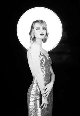 Cute face blond girl with red lips and vintage style hairstyle, wearing a golden sparkling dress with a halo behind her head. Isolated on black. Clean, healthy skin. Black and white. Copy space. Фото со стока