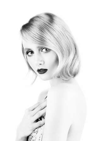 Cute blond girl with big beautiful eyes, red lips and vintage style hairstyle, wearing a golden sparkling dress touches her chest. Isolated on white. Clean, healthy skin. Black and white. Copy space.