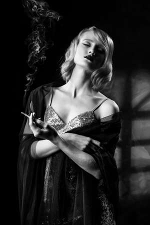 Cute face blonde girl with vintage style hairstyle, wearing a golden sparkling dress and black veil on her shoulders elegantly holds a smoking cigarette in her hand. Healthy skin. Black and white.