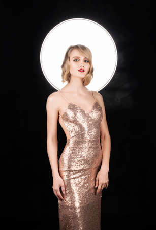 Cute face blond girl with red lips and vintage style hairstyle, wearing a golden sparkling dress with a halo behind her head. Isolated on black. Clean, healthy skin. Copy space.