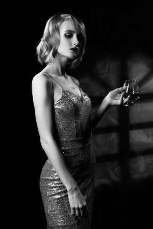 Cute face blond girl with vintage style hairstyle, wearing a golden sparkling dress elegantly holds a glass with a drink and stands on the background of a wall with window shadow. Black and white.