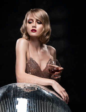 Cute face blond girl with red lips and vintage style hairstyle, wearing a golden sparkling dress elegantly holds a glass with a drink and leans on a large mirror disco ball. Healthy skin. Copy space.