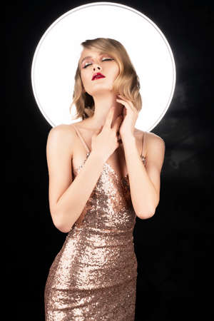 Cute face blond girl with red lips and vintage style hairstyle, wearing a golden sparkling dress with a halo behind her head touches her face and close her eyes. Clean, healthy skin. Copy space.