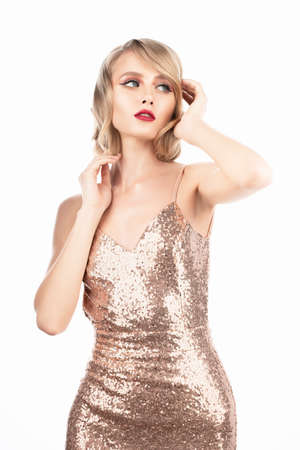 Cute blond girl with big beautiful eyes, red lips and vintage style hairstyle, wearing a golden sparkling dress touches her hair. Isolated on white background. Clean, healthy skin. Copy space.