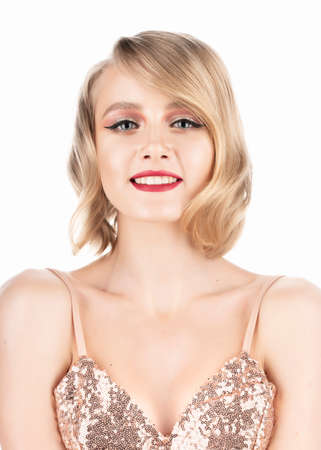 Cute smiling blonde girl with big beautiful eyes, red lips and vintage style hairstyle, wearing a golden sparkling dress. Isolated on white. Clean, healthy skin. Copy space.