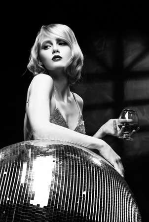 Cute face blond girl with red lips and vintage style hairstyle, wearing a golden sparkling dress elegantly holds a glass with a drink and leans on a large disco ball. Black and white. Copy space.