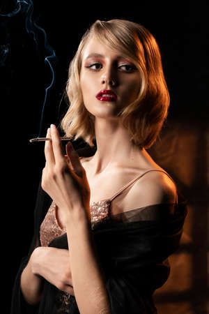 Cute face blonde girl with vintage style hairstyle, wearing a golden sparkling dress and black veil on her shoulders elegantly holds a smoking cigarette in her hand. Healthy skin. Copy space.