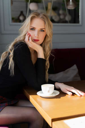 A beautiful long haired blond girl wearing a mini skirt is sitting and resting at a table with a cup of coffee in a cafe. Fashionable, commercial design. Copy space