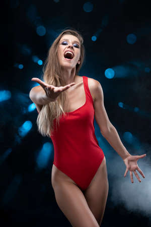 A beautiful long-haired slim girl wearing a red body, sings and screams and gives her hand against the background of spots of light from which blue rays shine in the smoke. Advertising and commercial