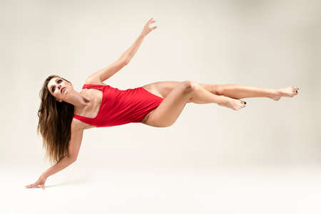 A beautiful long-haired long-legged slim girl wearing a red body levitates on a white background, touching the floor only with her hand. Advertising, conceptual, art and commercial design. Copy space Foto de archivo