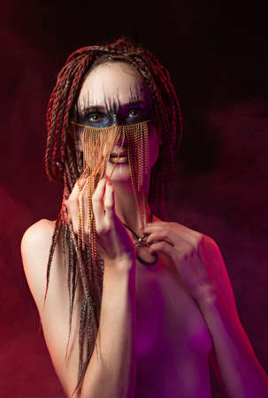 Beautiful young slim girl with creative make-up and a hairstyle of cornrows, wearing white t-shirt and jewelry of gold chains on her face covers her naked breast with her hands. Conceptual design.
